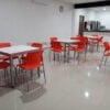 Mesas acrilico antibacterias blanco y sillas naranjas para comedores y cafeterias